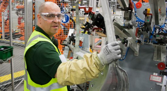 A worker at the Jaguar Land Rover plant helps put together a Range Rover Evoque.