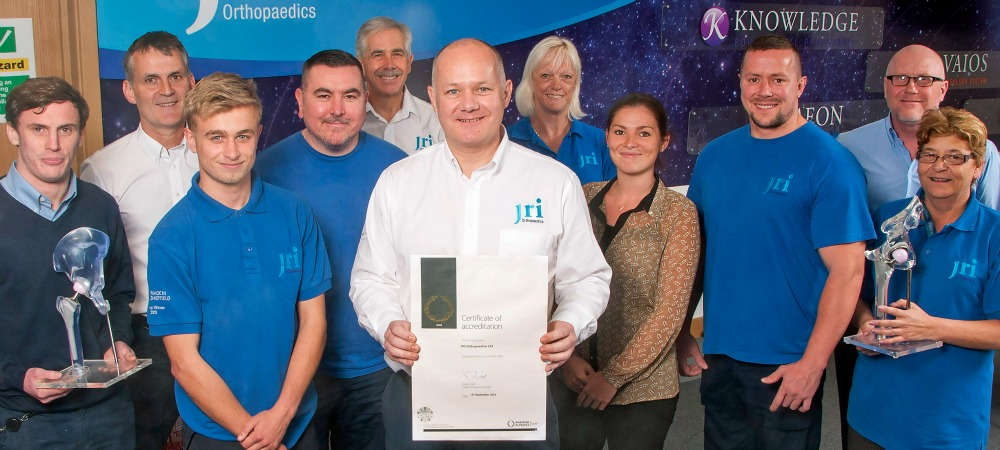 JRI Orthopaedics managing director, Keith Jackson (centre) and staff celebrate achieving the Investors In People Gold standard.