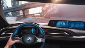 Inside the new BMW i8 concept with the interactive interior and video screen where the rearview mirror would normally be - image courtesy of BMW