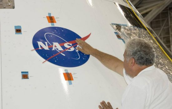Steve Lighthill, of Nasa, carefully smoothes out a Nasa logo decal after affixing it to the Orion test module flown at tests held at the Nasa White Sands Test Facility - image courtesy of Nasa