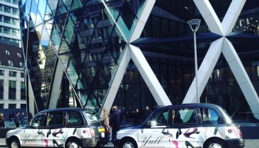 London Taxis advertising Yull outside the Gherkin.