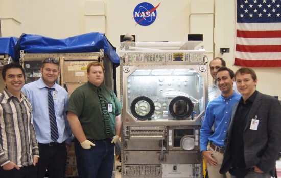 The Made In Space team with a functional duplicate of the Microgravity Science Glovebox enclosure in which its 3D printer is housed in space - image courtesy of Made in Space