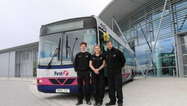 AMRC apprentices Sean Goodwin of Nikken and Abbie Plumer of Symphony Group PLC with AMRC Trainer Gareth Wilkinson and their new bus.