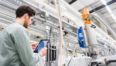 A tool manufacturing floor manager analyses smart factory connectivity equipment using the Internet of Things (IoT) - image courtesy of Cisco.