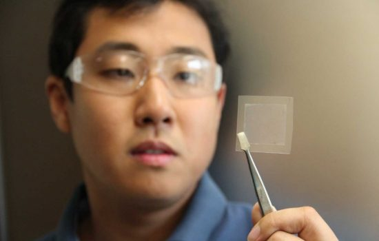 A CSIRO scientist holds up a thin slice of graphene. Image courtesy of CSIRO.
