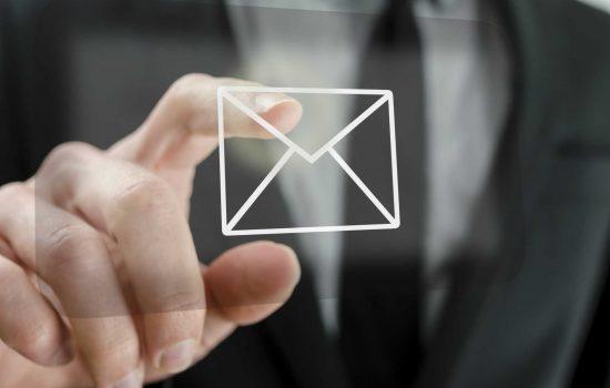 Businessman touching email icon - image courtesy of Depositphotos.