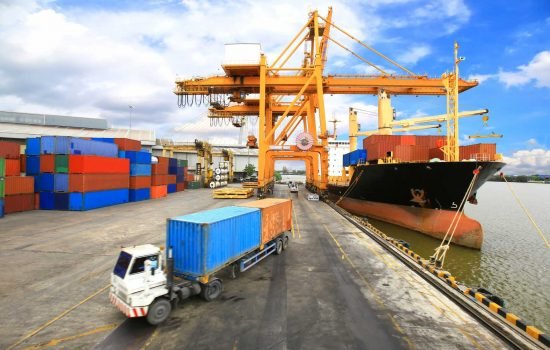 Industrial Container Cargo freight ship with working crane bridge - image courtesy of Depositphotos.