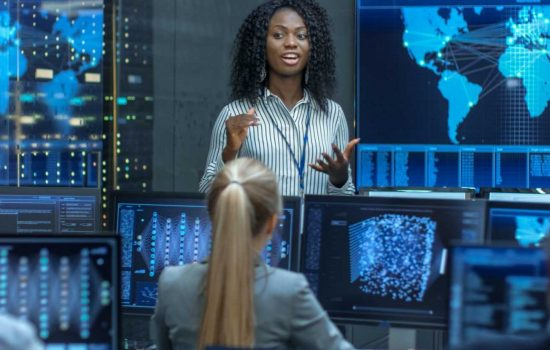 Chief Project Engineer Holds Briefing for a Team of Scientists that are Building Machine Learning System. Displays Show Working Model of Neural Network - image courtesy of Shutterstock
