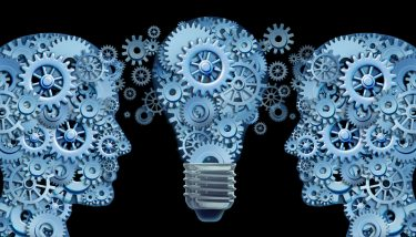 Knowledge Transfer Partnership - Working together as a team for innovative strategies and creating new ideas and products through lesdership and education represented by two human heads and a lightbulb in the shape of gears and cogs - image courtesy of Depositphotos.