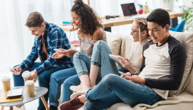 Happy multicultural teens sitting on sofa with digital devices - Generation Z Young People Skills - image courtesy of Depositphotos.