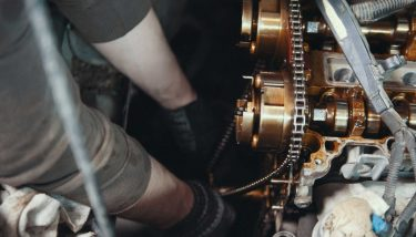 Mechanic cleans and wipes the car engine parts - cleaning wipes - image courtesy of Depositphotos.