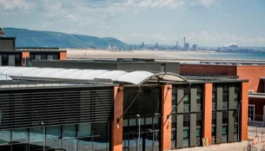 Swansea University Bay Campus, with Tata Steel Port Talbot across the bay - International evidence shows that success in steel comes from having research and industry located close to each other – image courtesy of Swansea University.