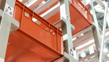 Red plastic boxes in the cells of the automated warehouse - image courtesy of Depositphotos.