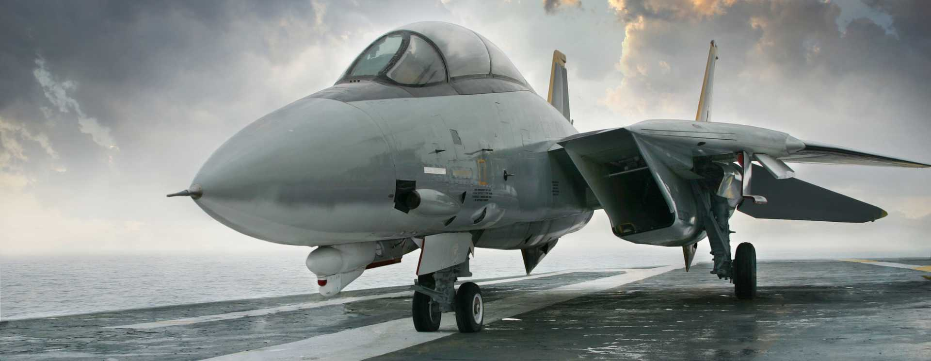 F-14 jet fighter on an aircraft carrier deck beneath dramatic sky – stock image courtesy of Depositphotos.