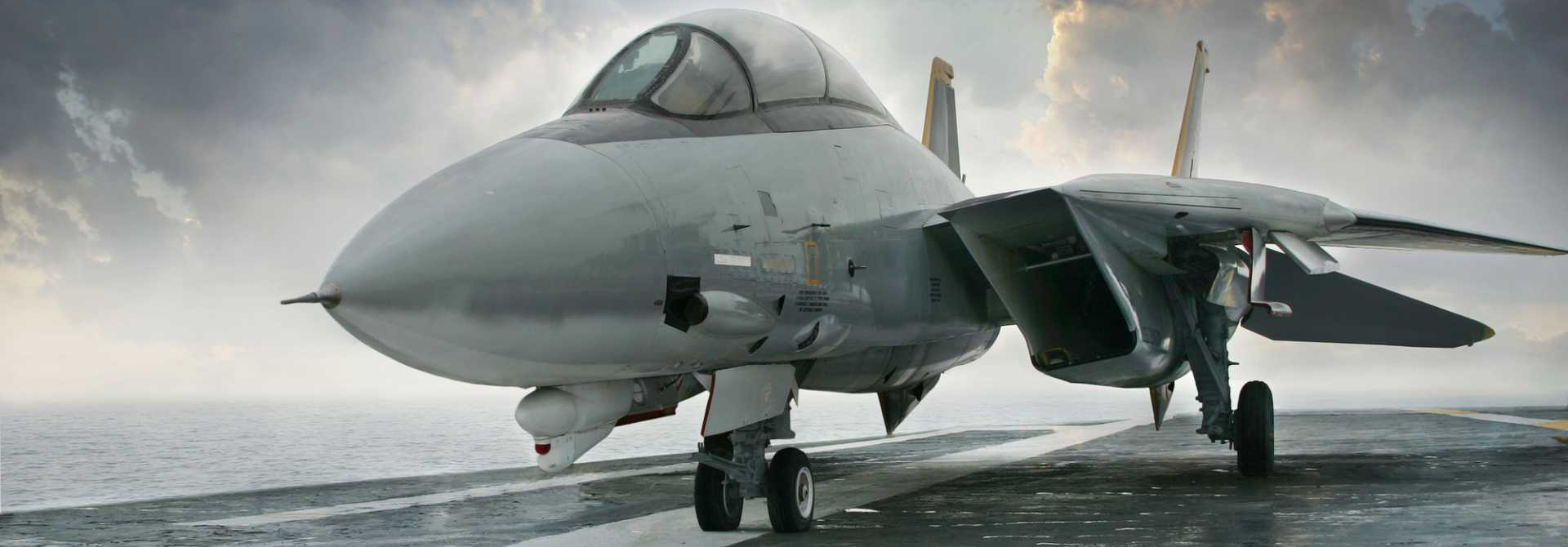 CROP F-14 jet fighter on an aircraft carrier deck beneath dramatic sky – stock image courtesy of Depositphotos.