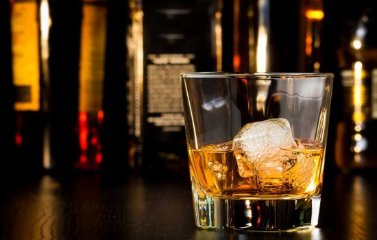Whiskey glass with ice in front of bottles - image courtesy of Depositphotos.