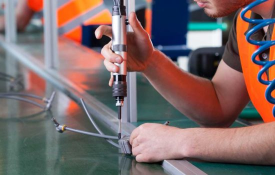 Men during precision work on production line - image courtesy of Depositphotos.