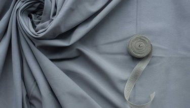 Grey folds fabric with cloth roll background textiles fashion - image courtesy of Depositphotos.