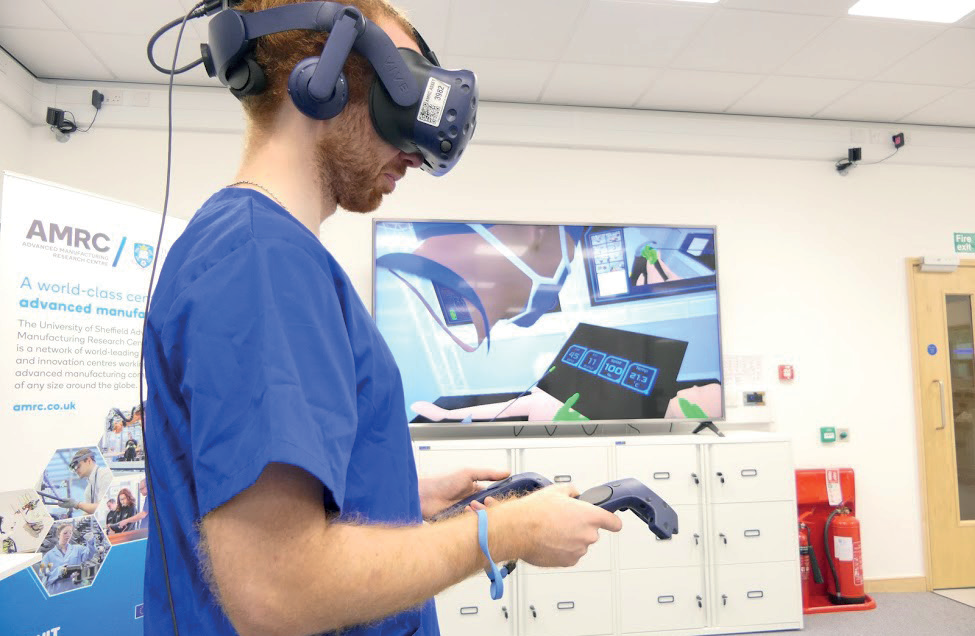 Project engineer Rob Stacey wears a virtual reality headset with his avatar in the Digital Operating Theatre shown on the screen behind him - image courtesy of AMRC.