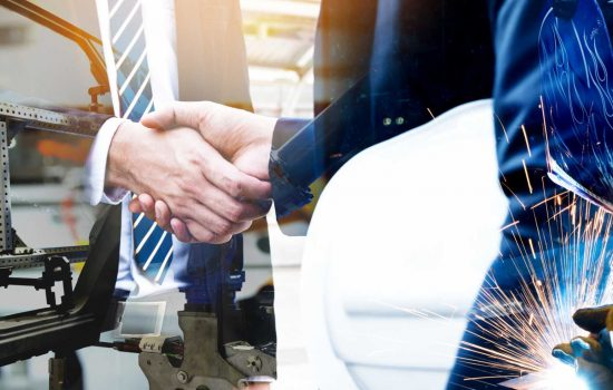 British Standards - Cyber communication and robotic trend , Industrial 4.0 Cyber Physical Systems technology concept. Double exposure of business men handshake teamwork , welding automate robot arm in smart factory - image courtesy of Shutterstock