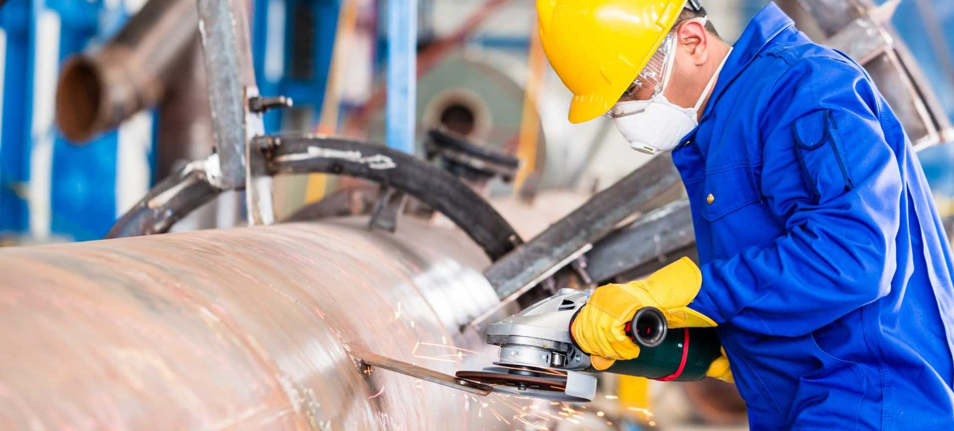 Industrial worker in manufacturing plant grinding to finish a pipeline - shutterstock_454261678 (1)