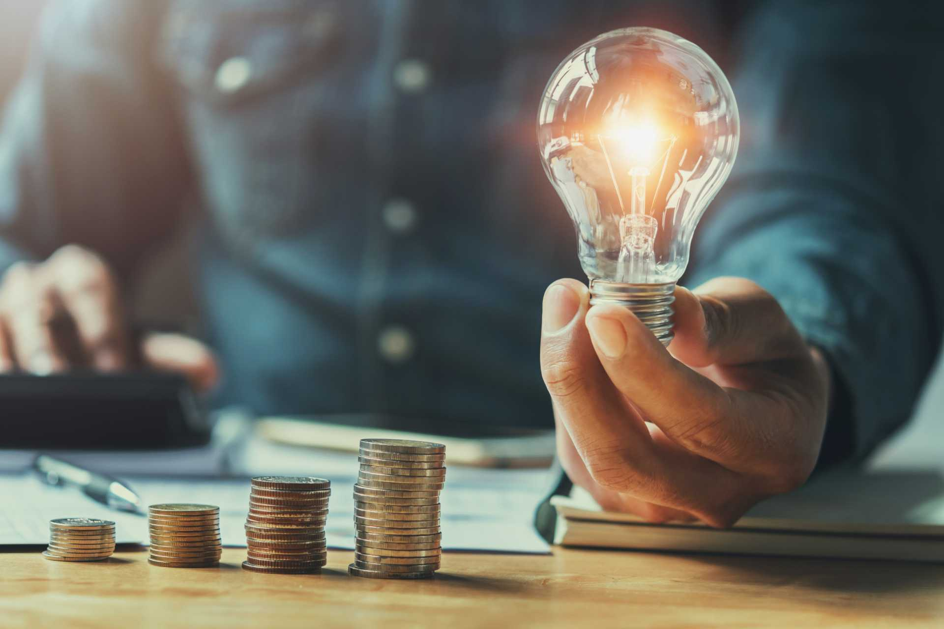 manufacturing finance business man hand holding lightbulb with using calculator to calculate and money stack. idea saving energy and accounting finance in office concept - Shutterstock