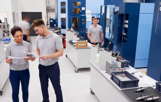 Engineers Meeting On Factory Floor Of Busy Engineering Workshop - shutterstock_1067929811