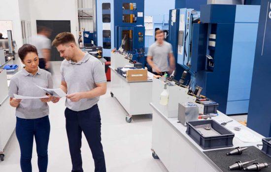Engineers Meeting On Factory Floor Of Busy Engineering Workshop - shutterstock_1067929811
