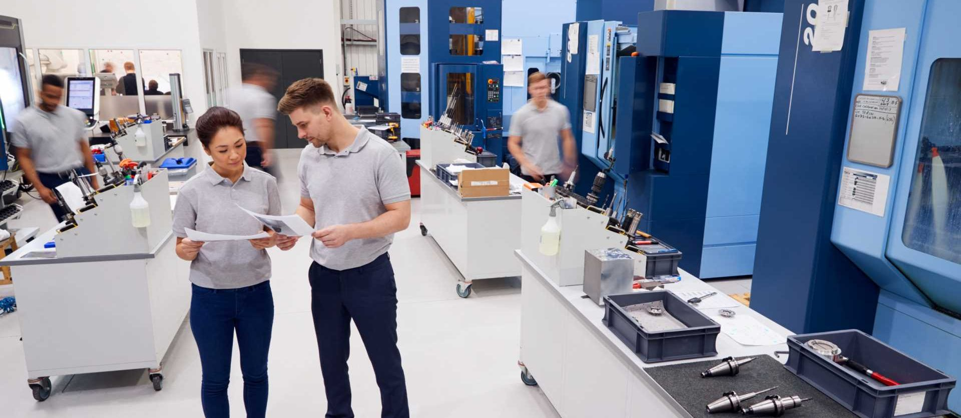 contract manufacturing = Engineers Meeting On Factory Floor Of Busy Engineering Workshop - shutterstock_1067929811