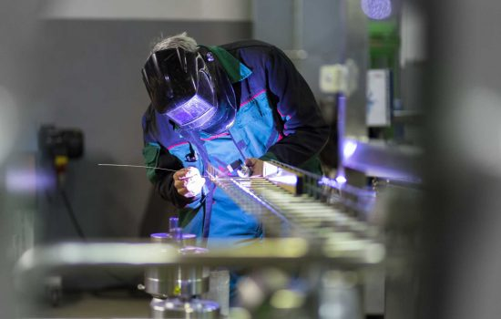 Industrial worker with protective mask welding inox elements in steel structures manufacture workshop. shutterstock_350928407