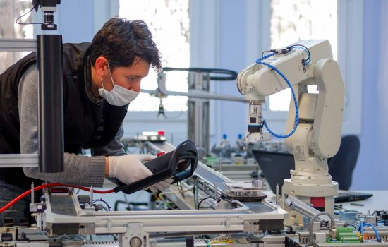 Man with surgical mask on face against COVID-19 ( Coronavirusis ) programming robot arm with control panel which is integrated on smart factory production line. industry 4.0 automation line - shutterstock_1711767100