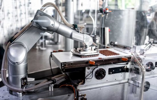 automatic robotic hand moving and preparing tiny bits of chocolate at chocolate factory - shutterstock_196486598