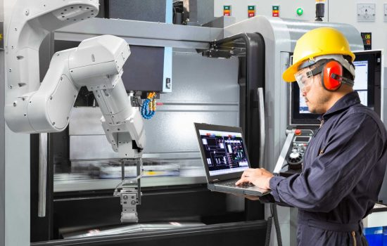 shutterstock - Maintenance engineer using laptop computer control automatic robotic hand with CNC machine in smart factory. Industry 4.0 concept