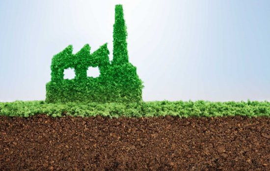 Sustainable industrial development concept with grass growing in shape of factory - Shutterstock