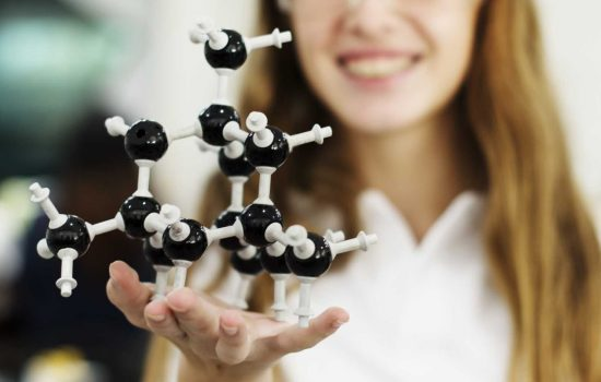 Student holding a molecule model in her hand - Shutterstock