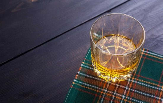 Shutterstock - Glass of Scotch whisky on a traditional tartan cloth on a wooden table