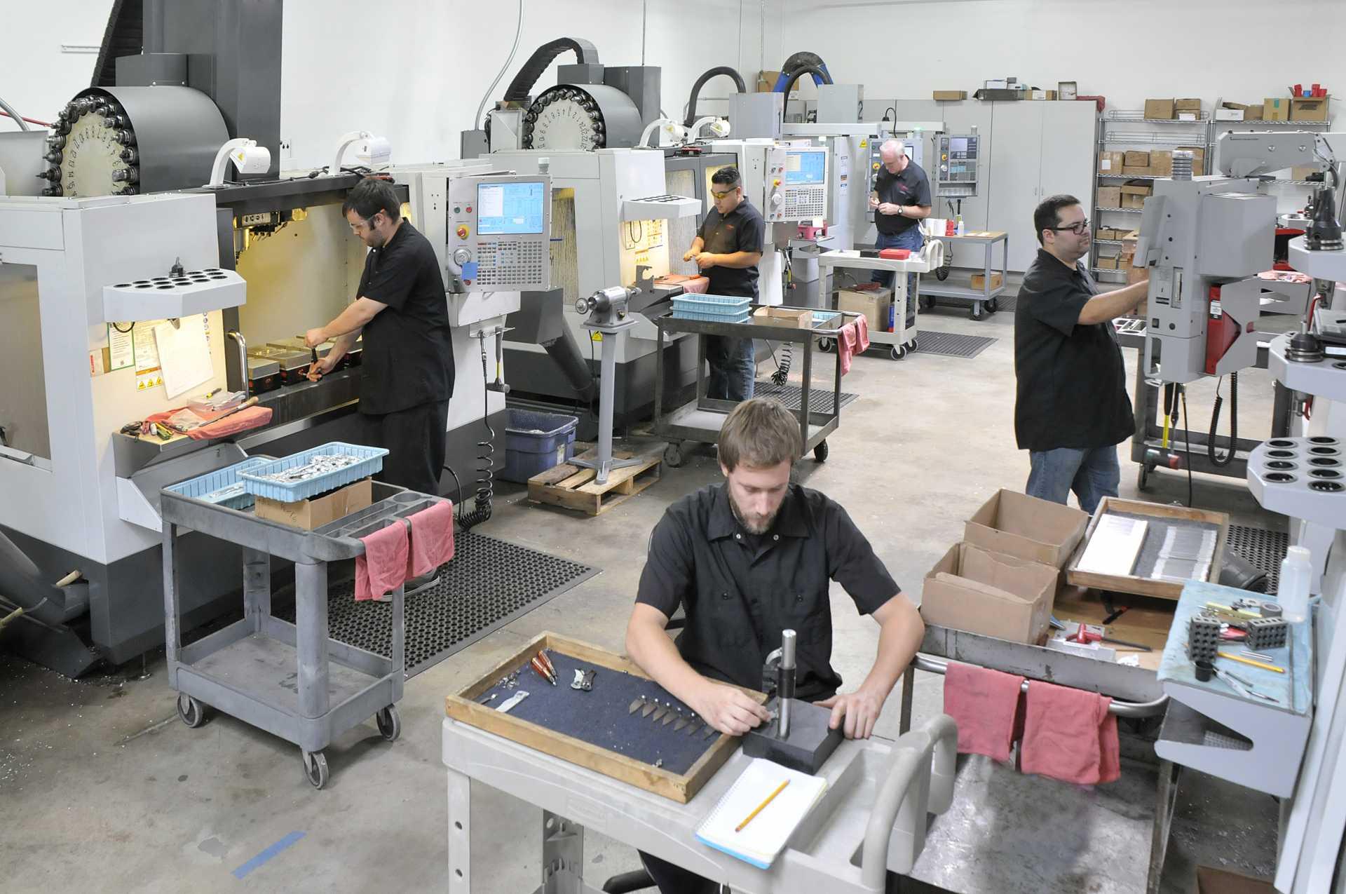 Cửa hàng máy chính xác CNC công nghệ cao hiện đại với nhiều nhân viên vận hành tại các loại máy khác nhau_Autodesk