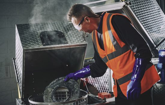 A maintenance worker uses a Safetykleen automatic parts washer to clean a crticial part - image courtesy of Safetykleen