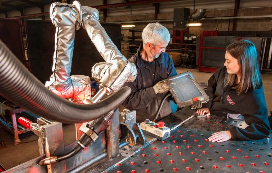 Rachel Brown, CAD technician, and Steve Elleray, R&D fabricator, witrh the robotic welder at Storth. Courtesy of Storth.