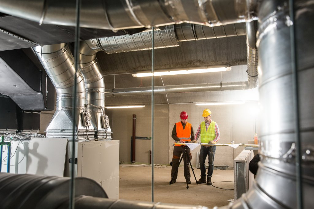 Workers making final touches to HVAC system. Image courtesy of Shutterstock